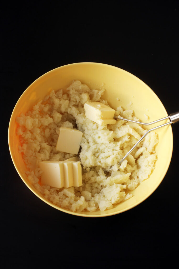 adding butter to potatoes