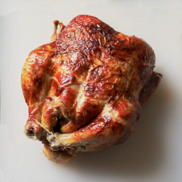 whole roast chicken on a white cutting board.