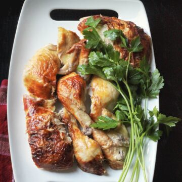 carved chicken pieces on a platter with fresh herbs.