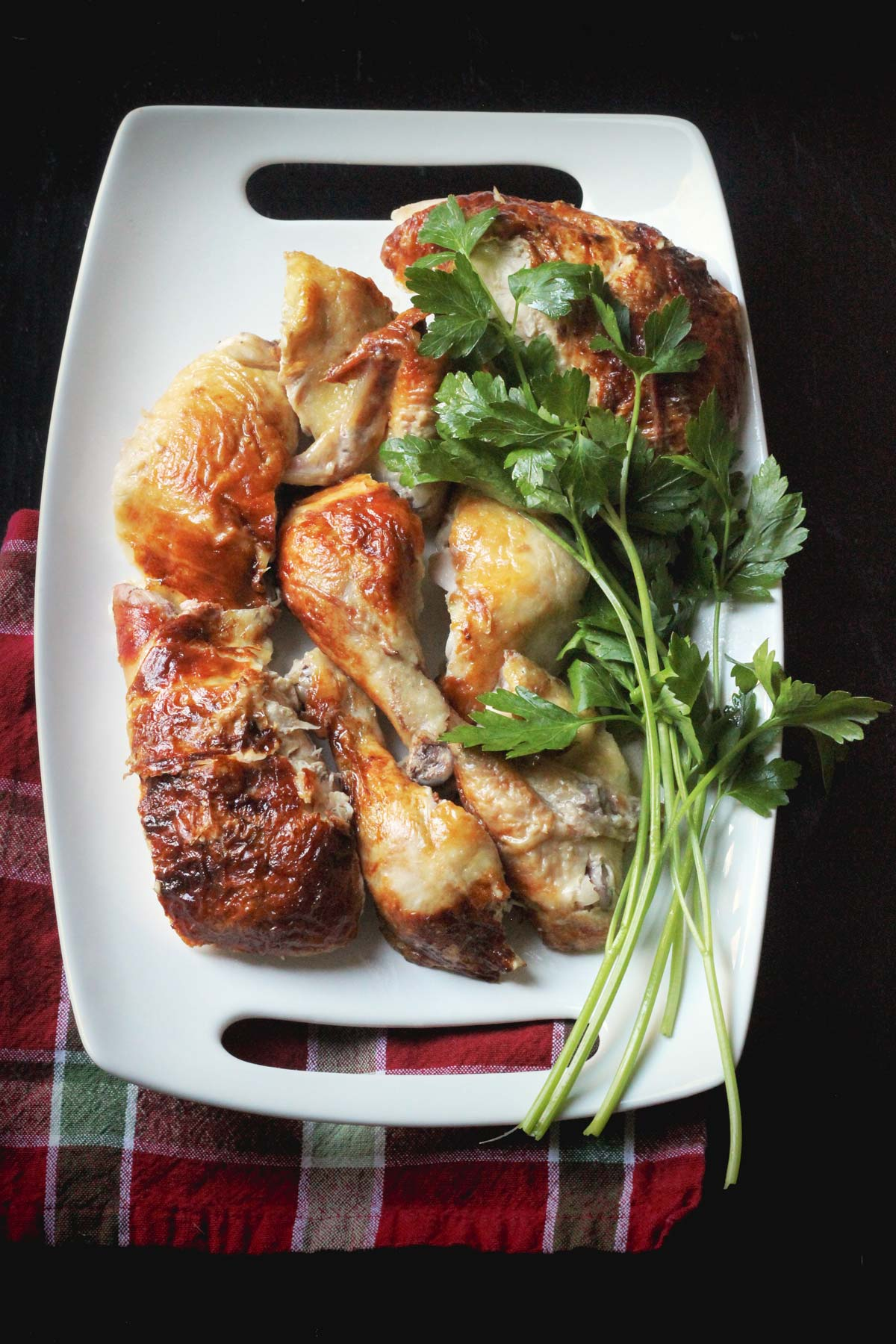 whole chicken carved into eight pieces on serving platter with fresh herbs.