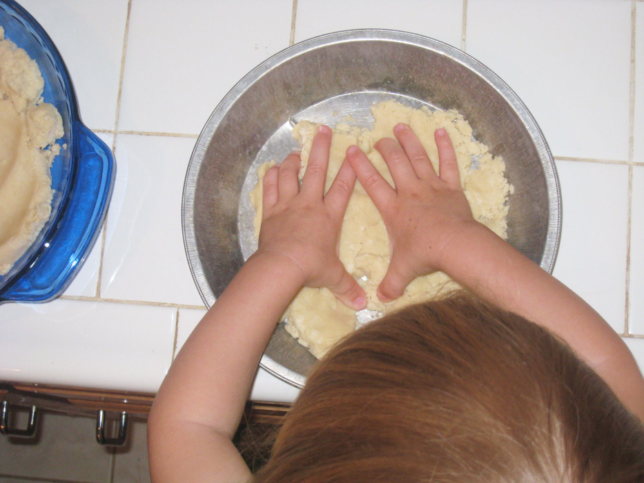 toddler girl pressing dough into pie plate