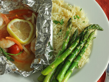 fish packet, rice, and asparagus on plate