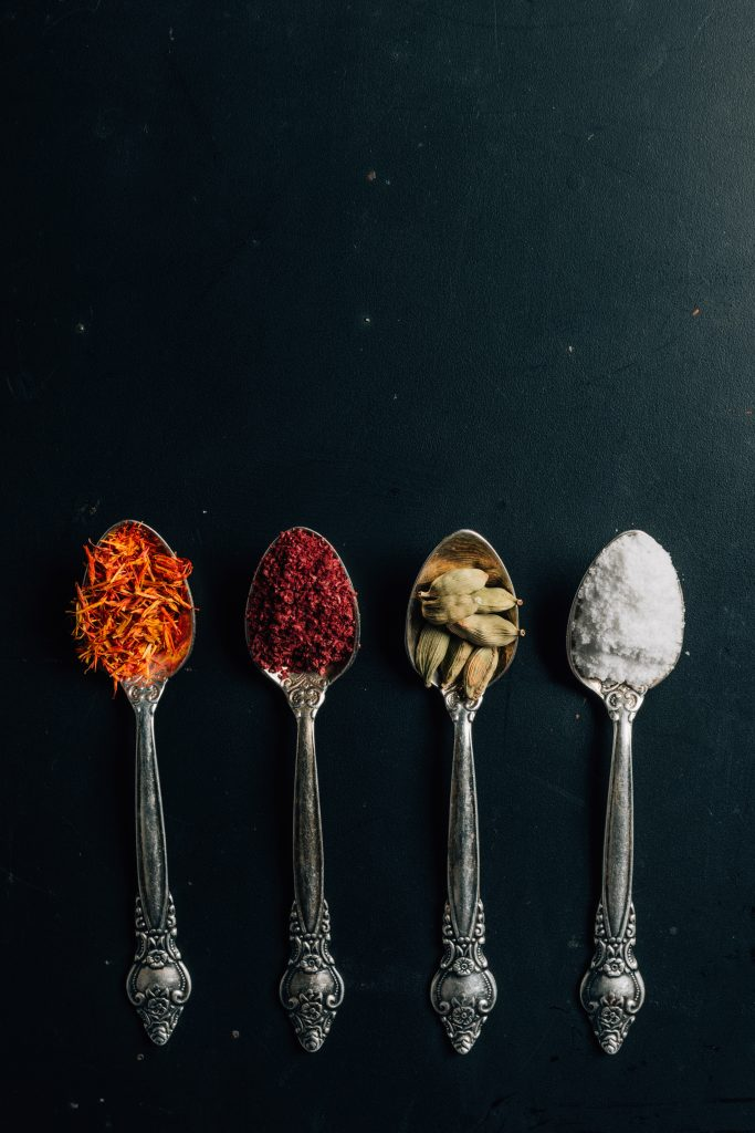 four spoons with different spices in them