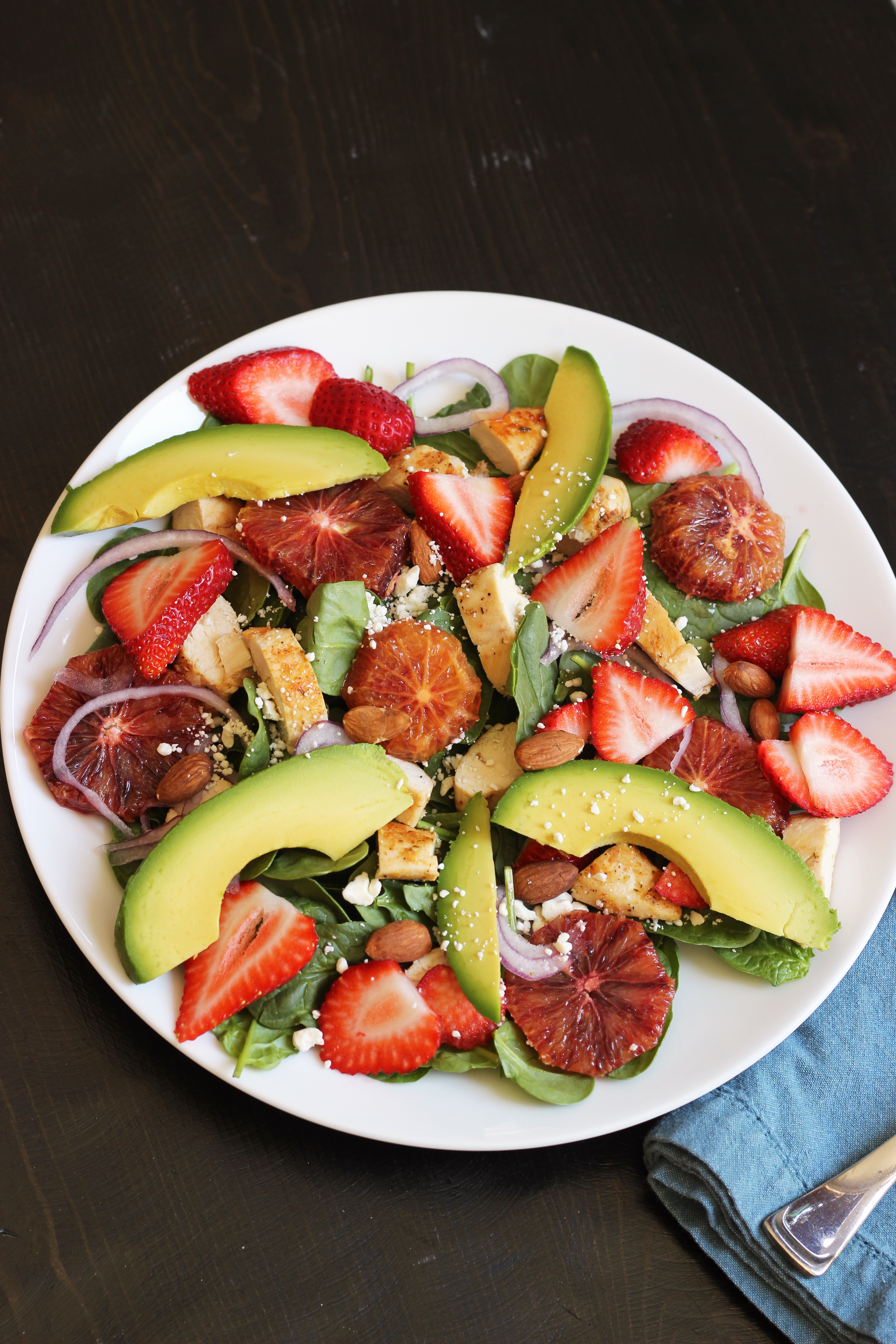 spinach salad with chicken, strawberries, and other fruit
