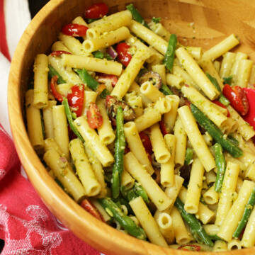 A bowl filled with pasta and vegetables, with Pesto