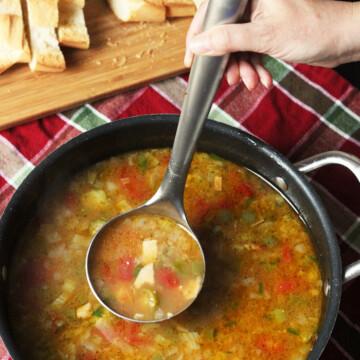 A person ladling soup