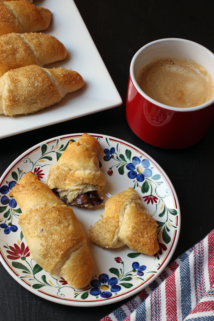 A plate of chocolate crescents and a cup of coffee