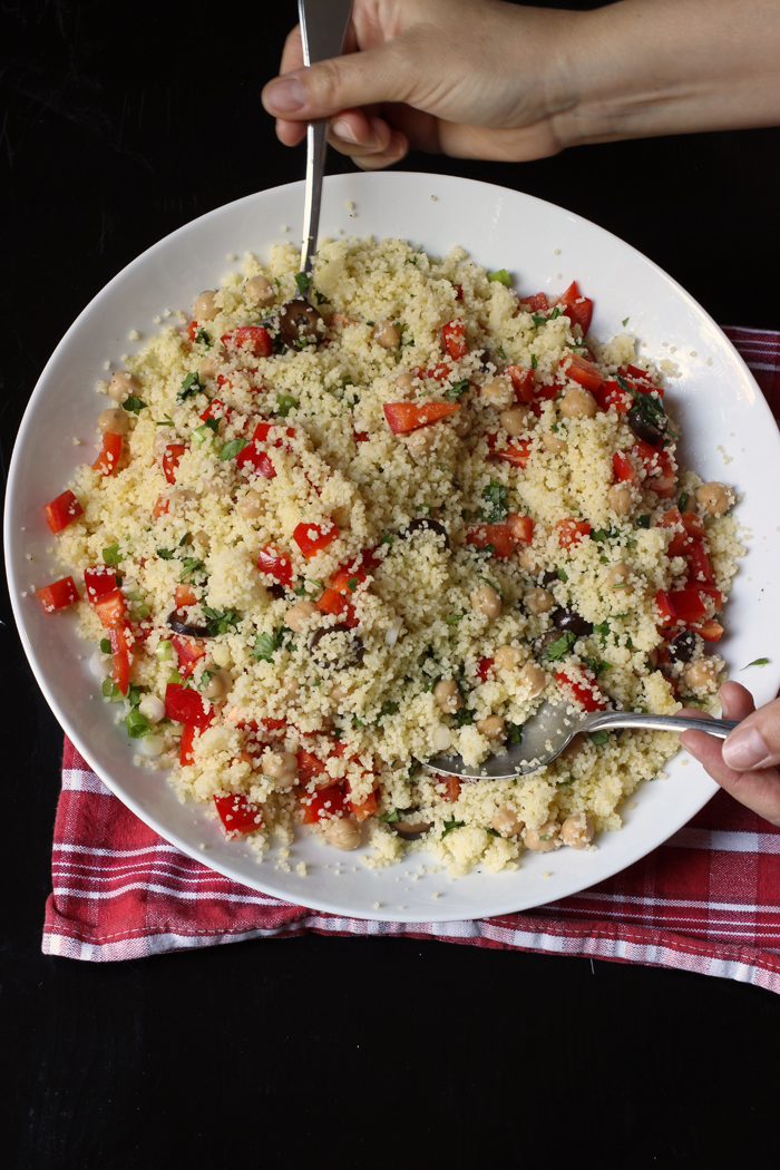 bowl of couscous salad with serving hands