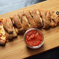 A pizza sitting on top of a wooden cutting board, with Calzone