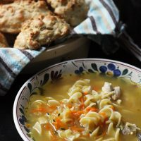 bowl of chicken noodle soup and basket of biscuits