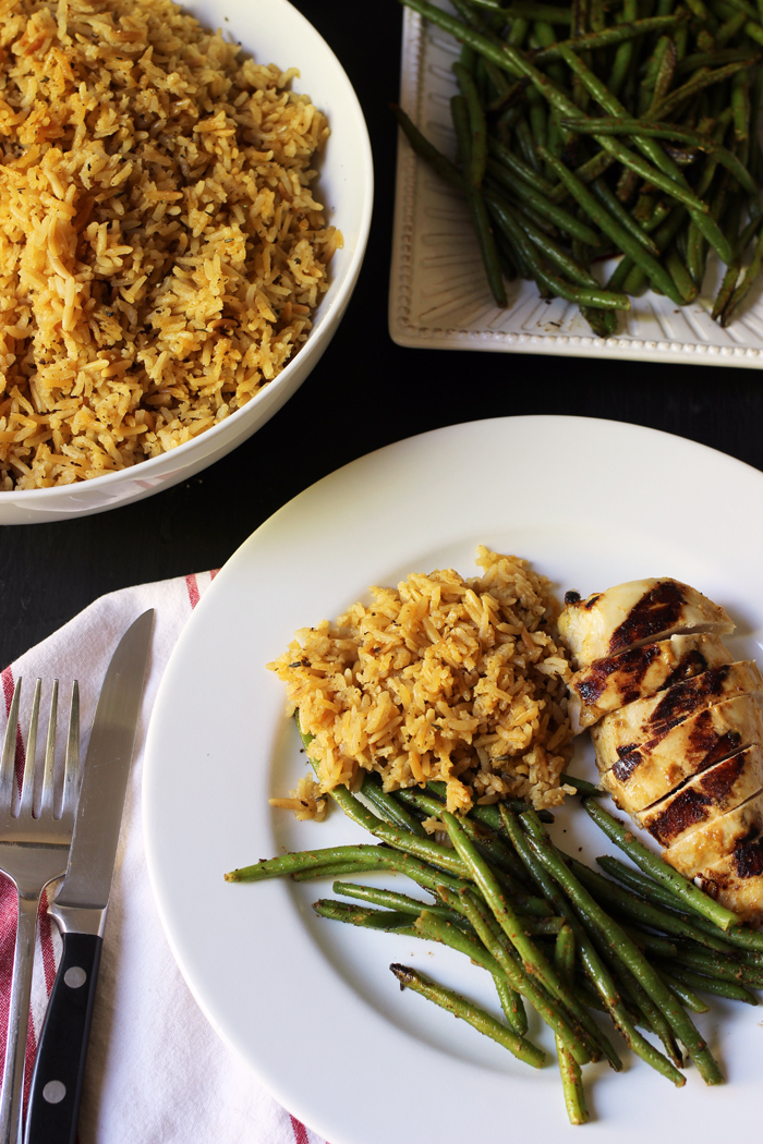 seasoned rice pilaf on a plate with chicken and green beans