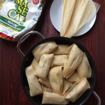 tamales stacked in steaming pot with maseca and corn husks nearby