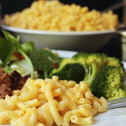 close up of macaroni on plate with large bowl