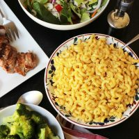 table set with mac and cheese salad pork and broccoli