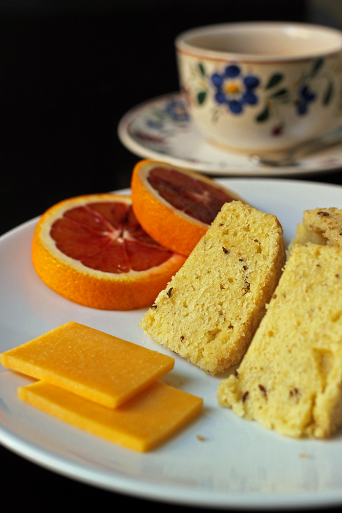 cheese cake and fruit on a plate with tea cup