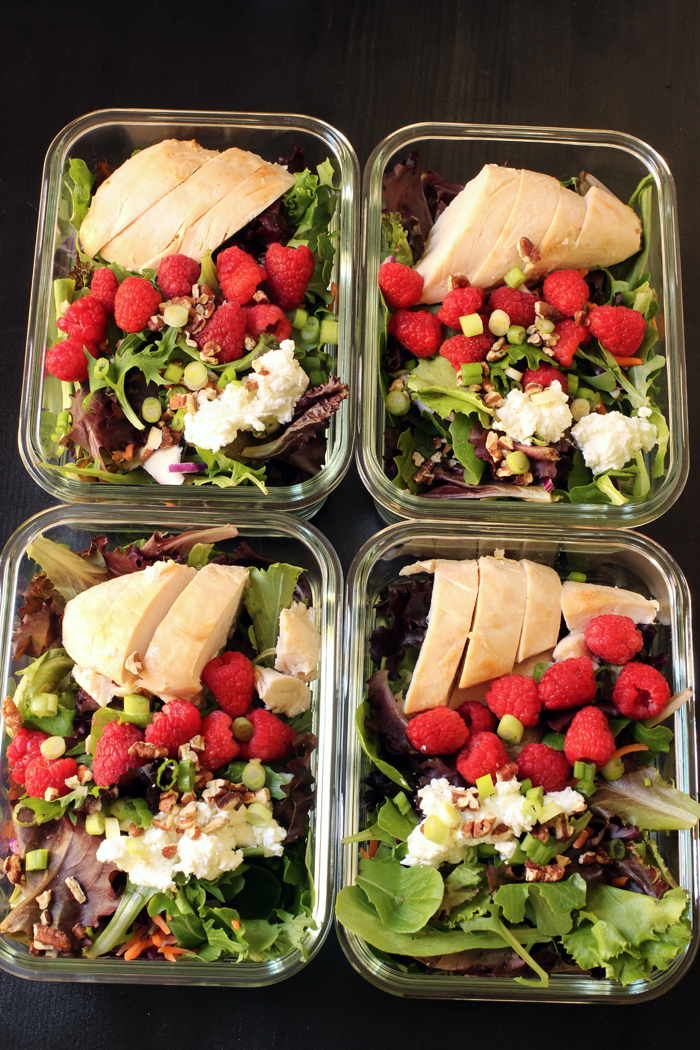 four meal prep salads with raspberries and chicken