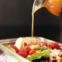 pouring raspberry vinaigrette onto salad