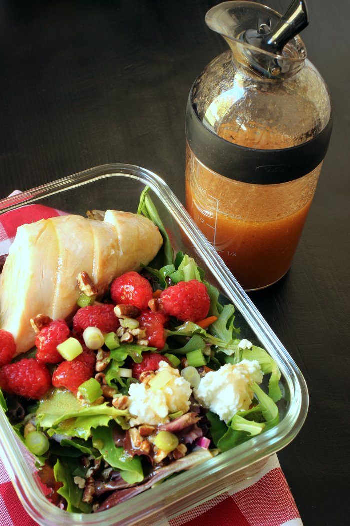 salad with chicken and raspberries with carafe of dressing