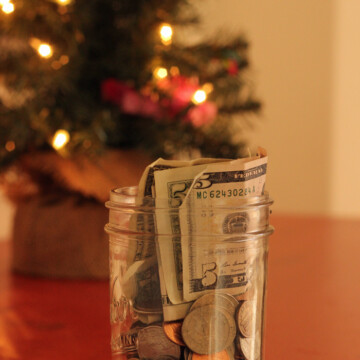 jar of money with christmas tree in background