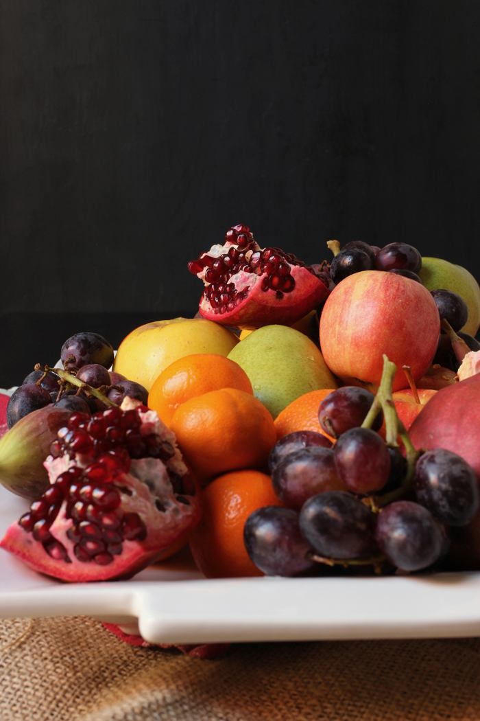 tray of winter fruit with broken pomegranates