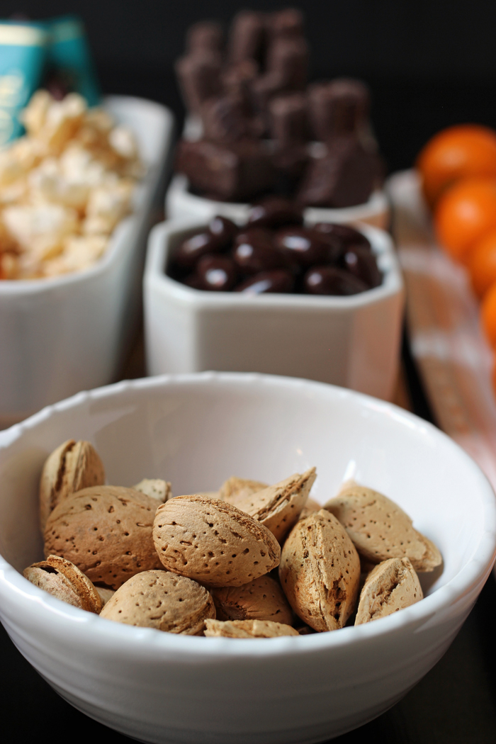 almond in shells in white bowl in front of dessert board