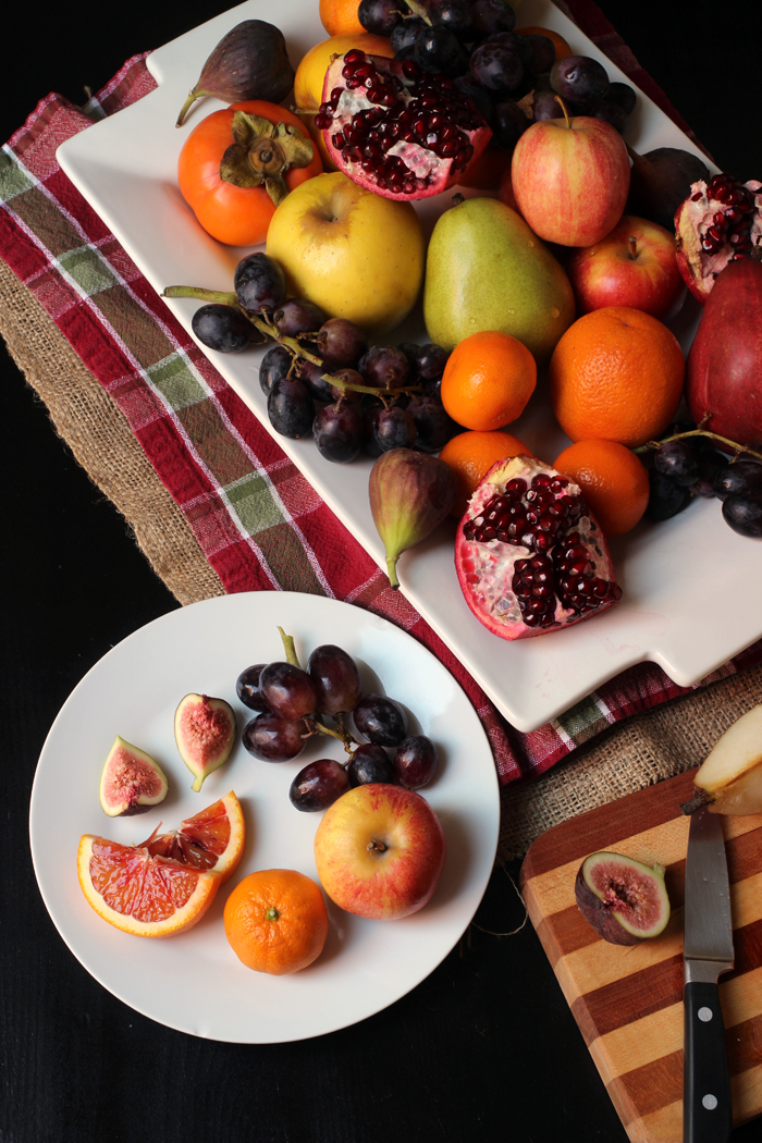 plate of cut fruit next to platter with knife and cutting board