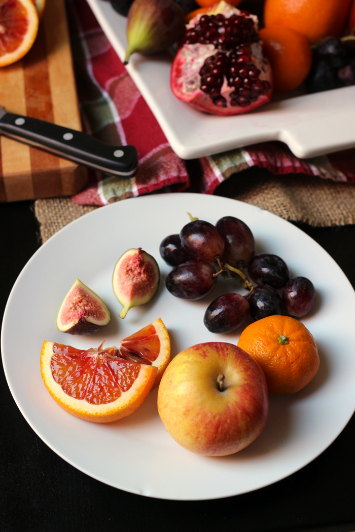 plate of fig orange apple and grapes
