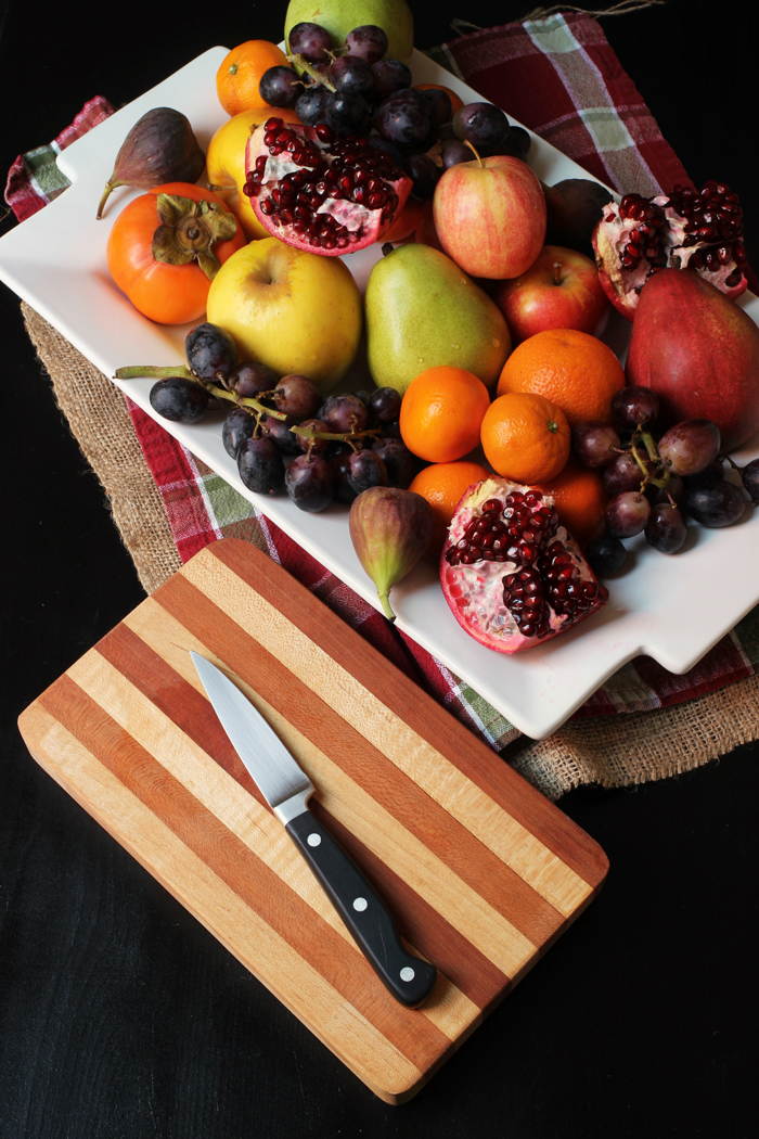 platter of fruit with cutting board and knife