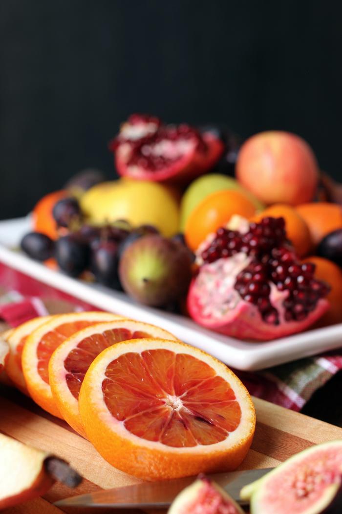 sliced blood orange on board next to fruit platter