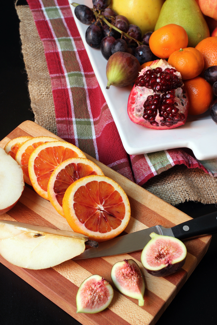 sliced orange pear and fig on cutting board with knife