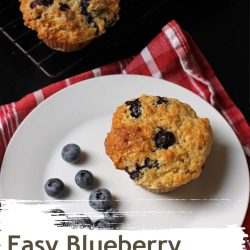 muffins on rack next to plate with a muffin and blueberries.
