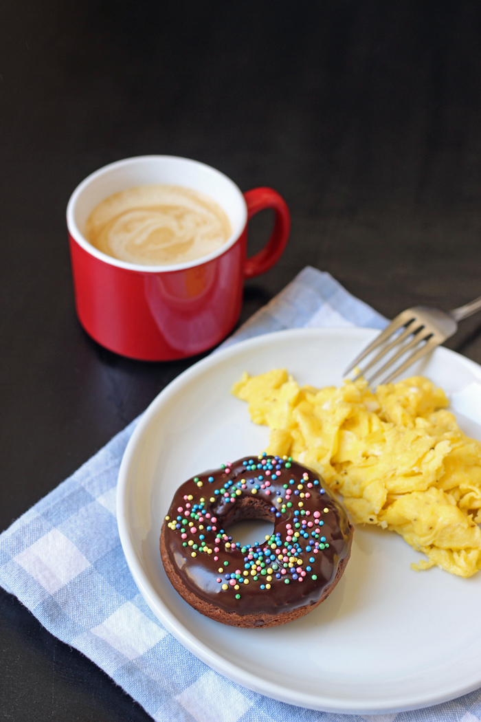 coffee with plate of scrambled eggs and chocolate donut