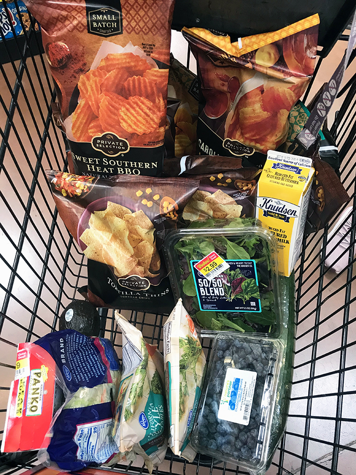 bags of chips with other groceries in cart