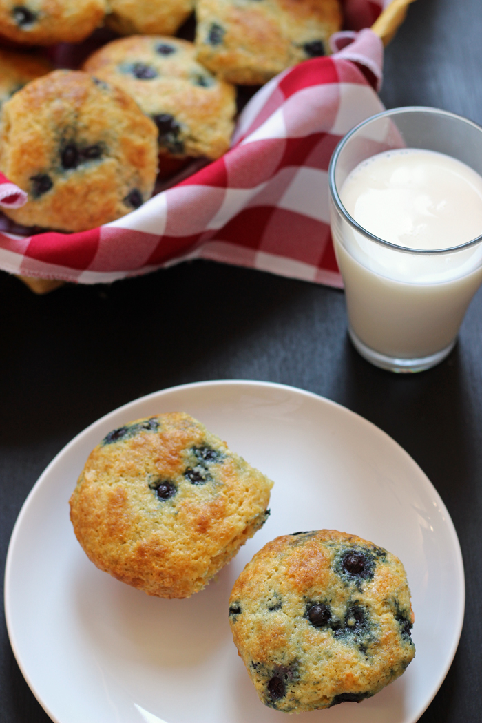 basket of blueberry corn muffins with plate and glass of milk