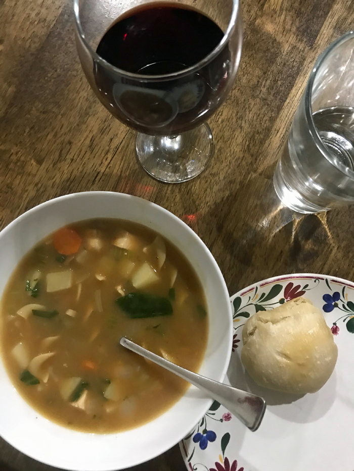 bowl of soup glass of wine and plate with roll