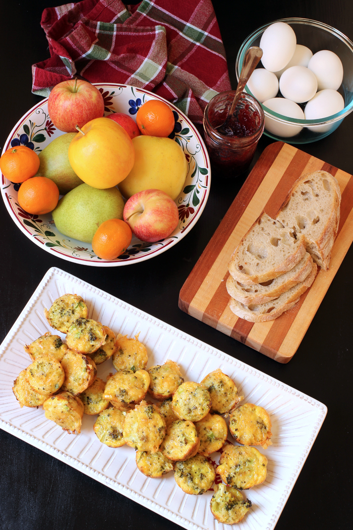 breakfast table set with fruit, eggs, bread, and quinoa egg bites