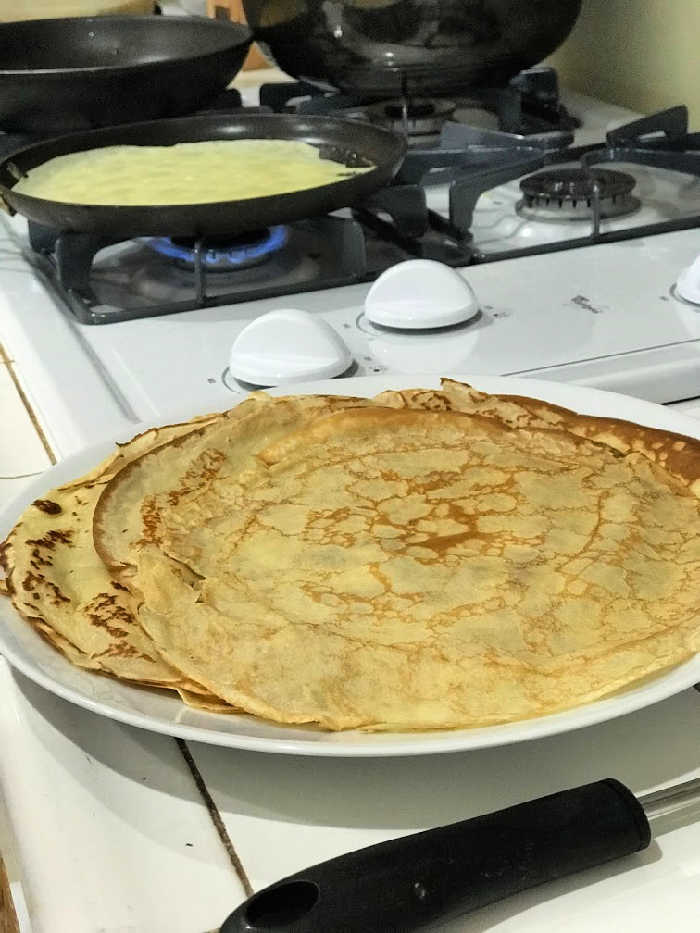 crepe cooking in pan and crepes on plate