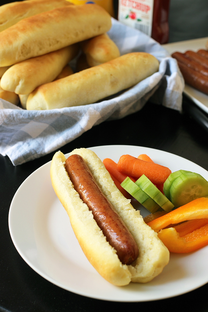hot dog on homemade bun on plate with vegetables