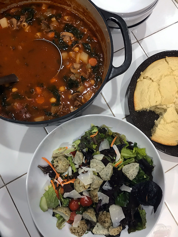 pot of minestrone soup pan of cornbread and salad in bowl