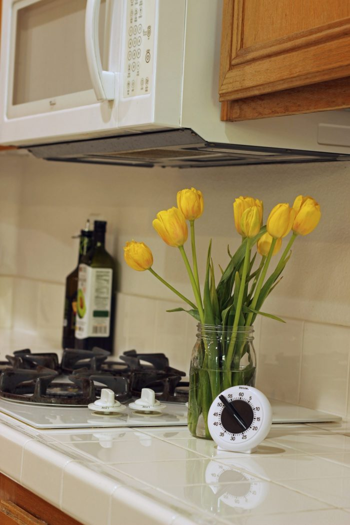 kitchen timer on counter next to jar of tulips
