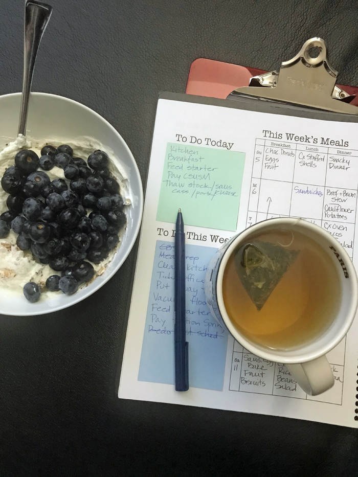 yogurt and berries with planner and cup of tea