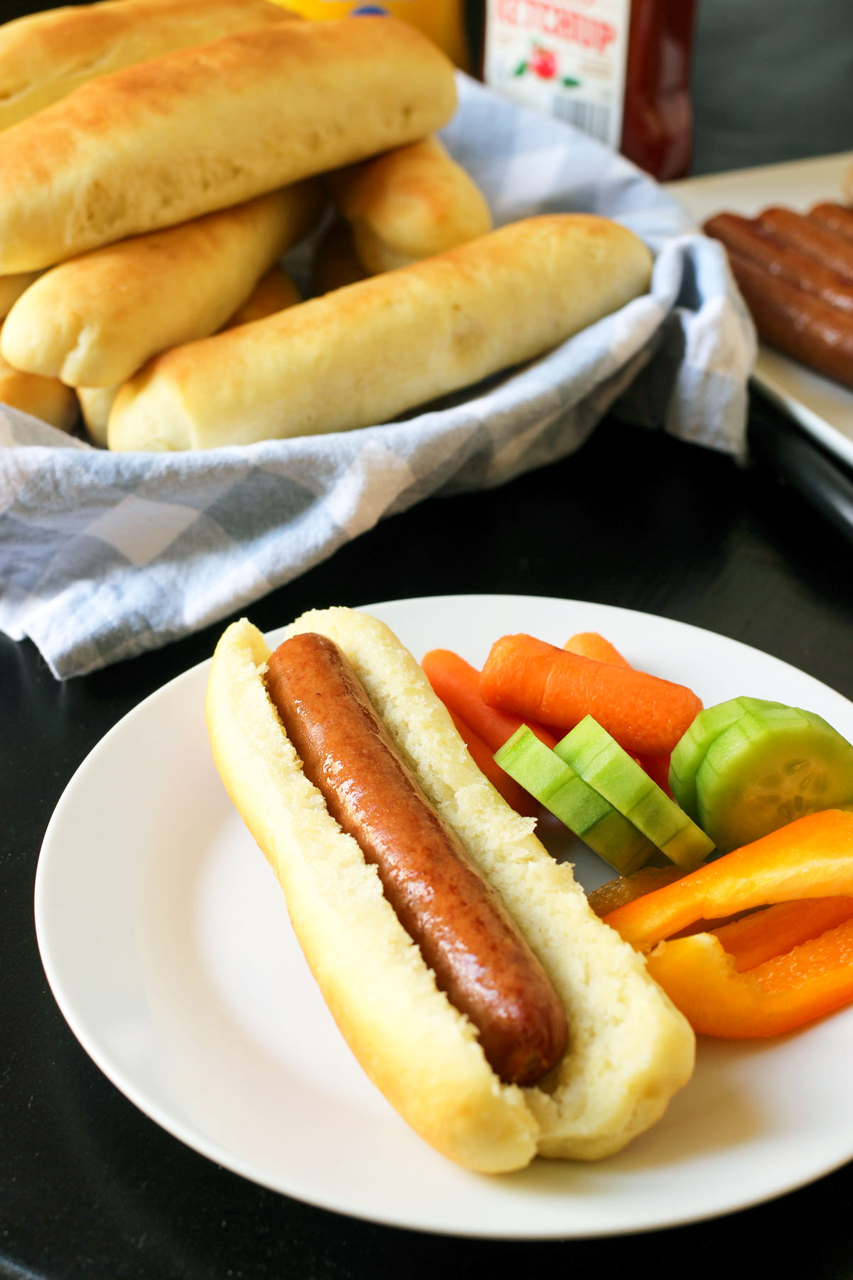 table set with dinner fixings and a small white plate with a hot dog on homemade hot dog bun with veggie dippers.