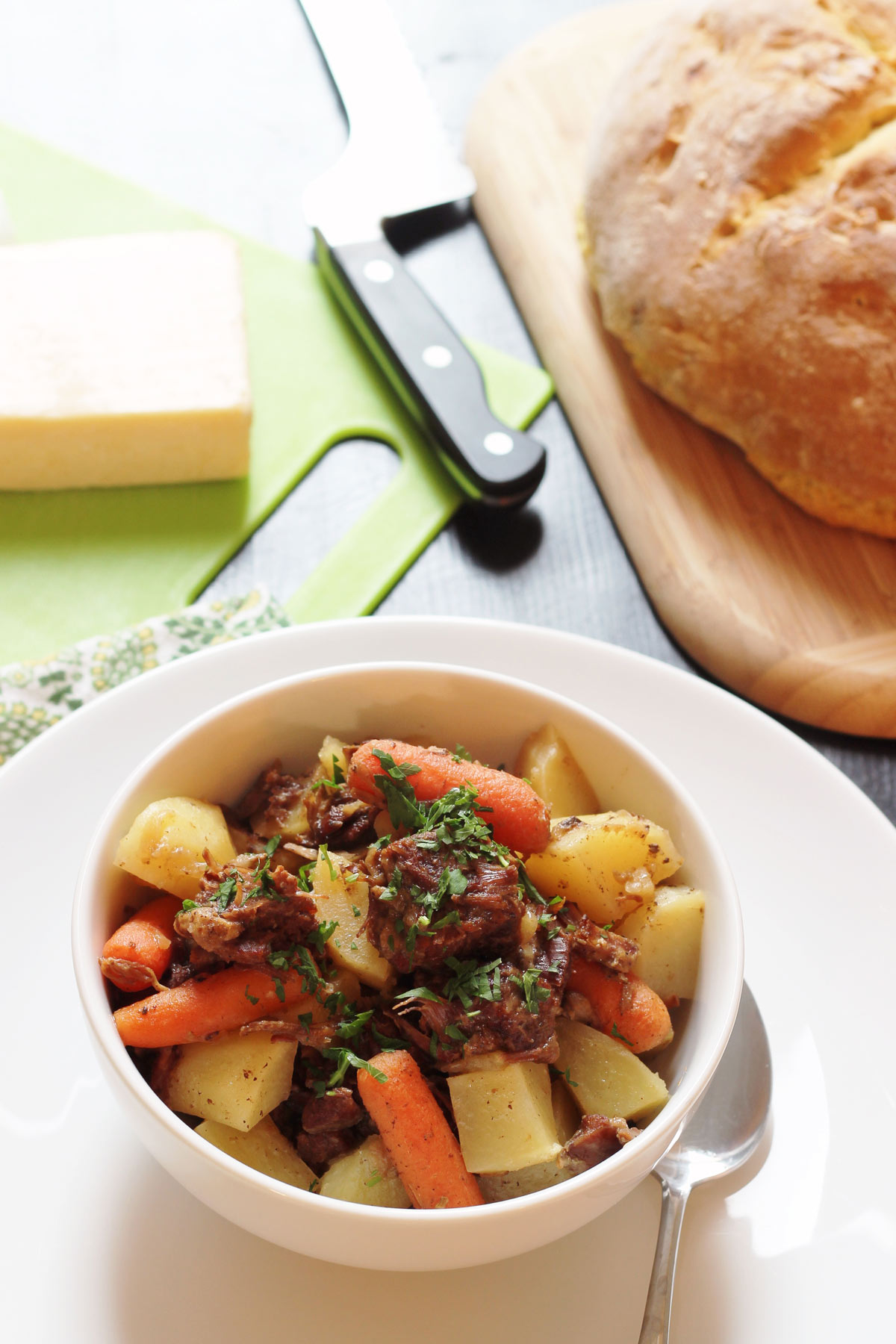 bowl of stew on table with bread and cheese