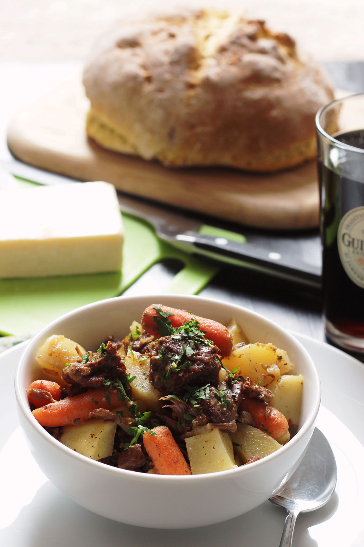 bowl of stew on table with bread cheese and ale