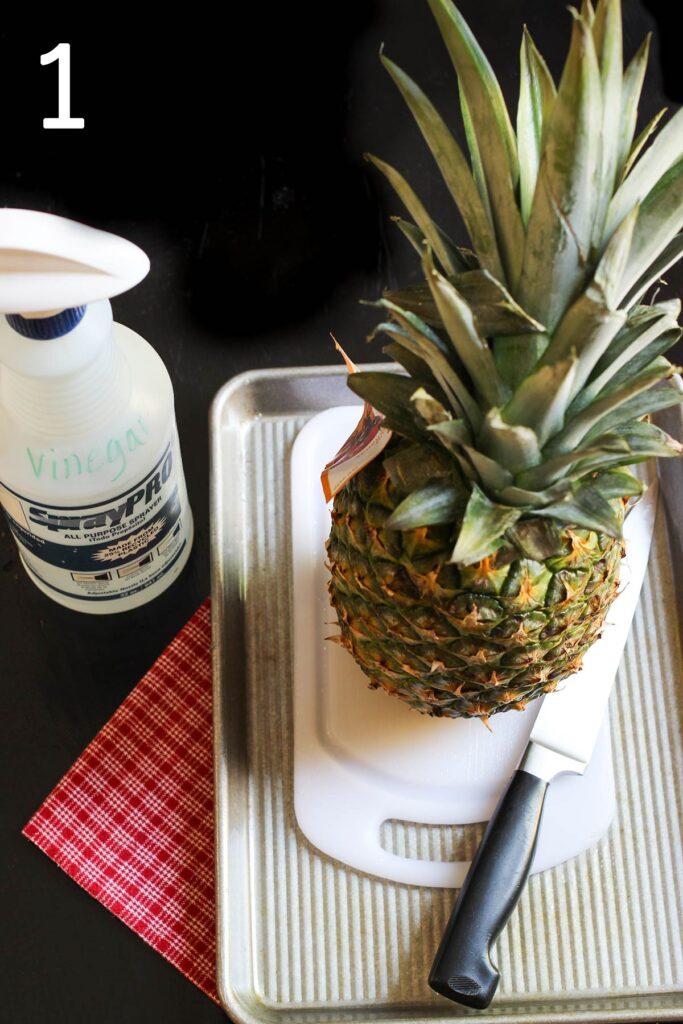 pineapple on cutting board in sheet pan with knife, bottle of vinegar nearby.