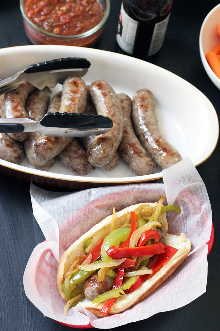 pan of brats with basket of bratwurst piled with peppers