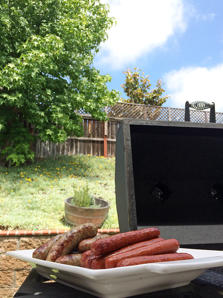 platter of brats and hot dogs next to open grill on blue sky day