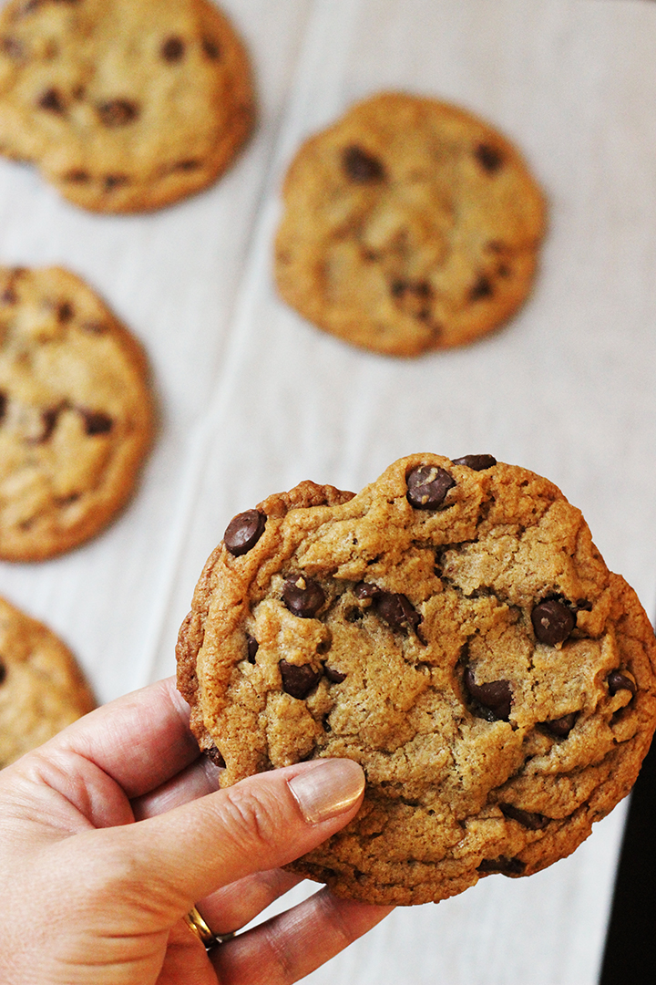woman's hand holding jumbo chocolate chip cookie above a pan of cookies