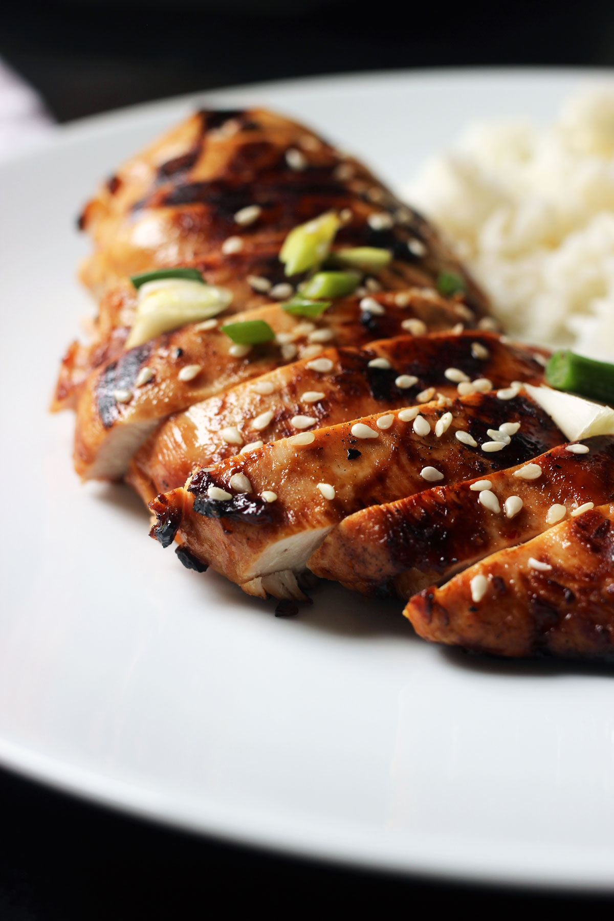 sliced asian chicken breast fanned on a white plate with rice.