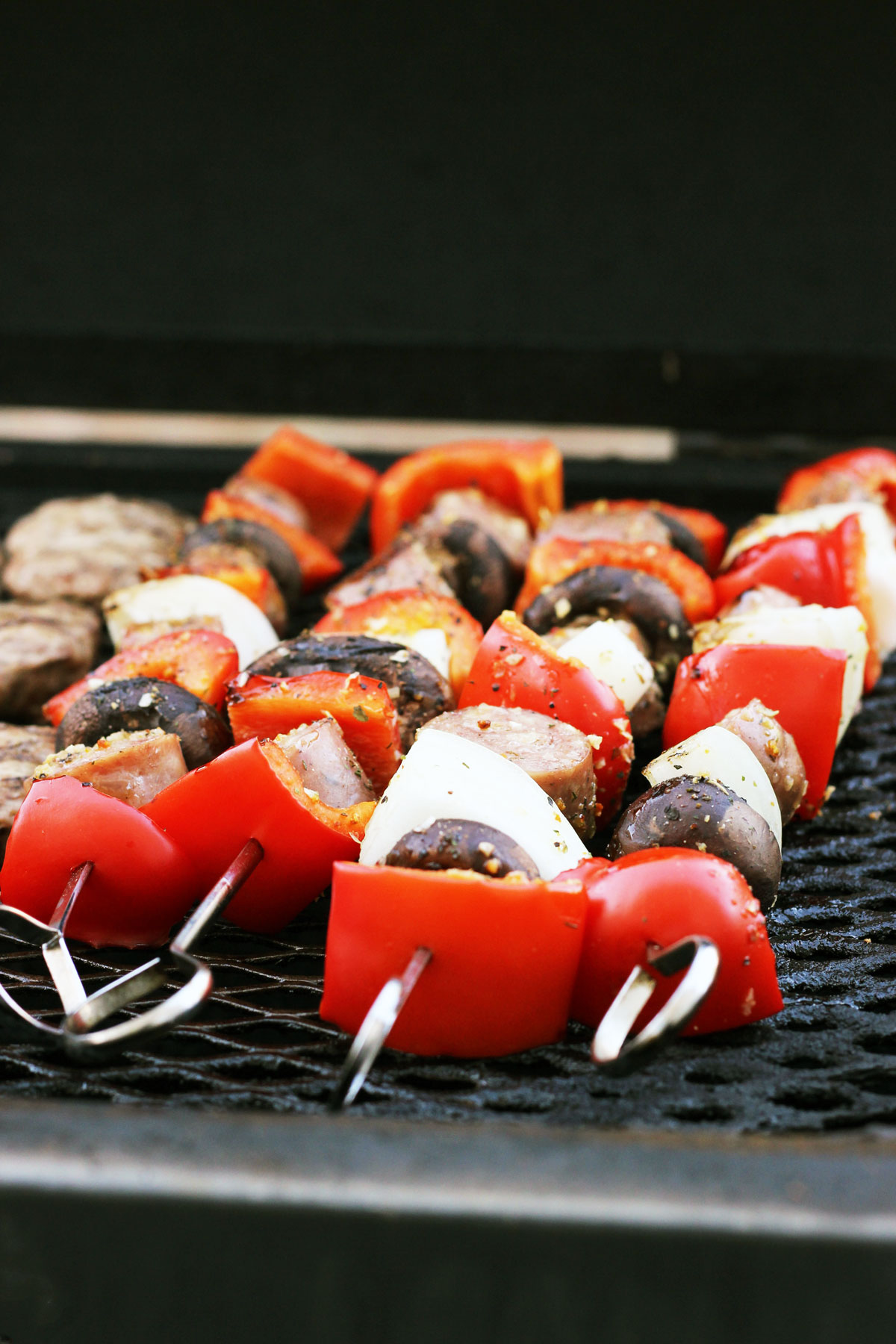 sausage, peppers, and onions on metal skewers on the grill.